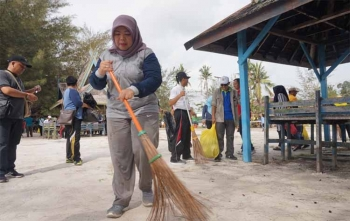 Bupati Kobar Hj Nurhidayah menyapu sampah di lokasi Pantai Kubu Minggu (15/10/2017)