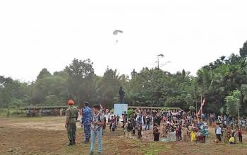 Nampak warga Desa Sambi menyaksikan terjun payung Pasukan Khas (Paskhas) TNI AU di Monumen Palagan Sambi, Desa Sambi, Kecamatan Aruta, Kabupaten Kotawaringin Barat. Selasa (17/10/2017).