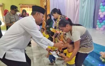 Wakil Bupati Sukamara, Ahmad Dirman saat menyerahkan hadiah kepada peserta lomba LBI.