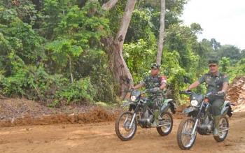 Kadispenad TNI AD, Brigjen TNI Alfret Denny D Tuejeh dan Dandim 1012 Buntok naik sepeda motor saat mengecek proyek jalan yang dibangun para prajurit melalui program TMMD