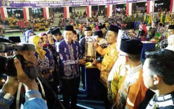 Bupati Barito Utara, H Nadalsyah saat menyerahkan piala bergilir FSQ ke perwakilan Juara Umum yakni Kota Palangka Raya.