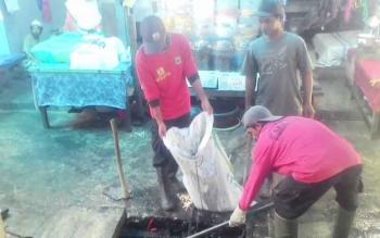 Petugas Petugas kebersihan membersihkan drainase didalam pasar Blok R Sabtu(21/10/2017).