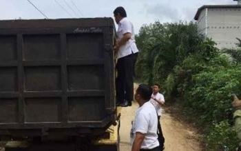 Bupati Barito Timur Ampera AY Mebas menaiki bagian belakang bak truk yang mengangkut material peningkatan jalan di Desa Runggu Raya, Kecamatan Paku pada Rabu (11/10/2017).