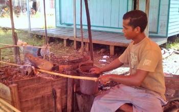 PROSES PEMBUATAN : Saat Abdullah (30) sedang melakukan pelurusan bambu untuk alat pancing.