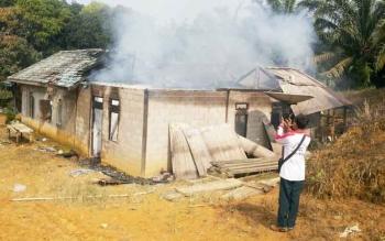 Sejumlah warga sedang berusaha memadamkan api yang membakar rumah di Kecamatan Telaga Antang, Senin (23/10/2017)