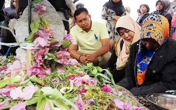 Ibu korban berinisial MU (kanan) saat berada di tempat pemakaman anaknya, Selasa (24/10/2017).