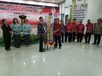 Ketua Panitia Festival Tandak Intan Kaharingan ke VII tingkat Kabupaten Gunung Mas Ilwis (kanan) menyerahkan piala juara umum, Senin (23/10/2017) malam.