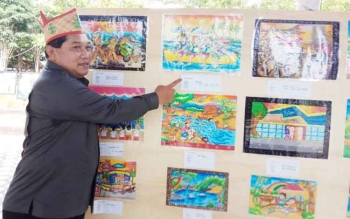 Ketua Dewan Kesenian Daerah Kabupaten Kapuas Darwandi saat menunjukan lukisan anak-anak pada pameran seni rupa natural dan kultural di Taman Raja Bunu, Minggu (29/10/2017).
