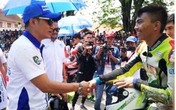 Bupati Kotim Supian Hadi saat berjabat tangan dengam seorang pembalap yang berada di garis star.