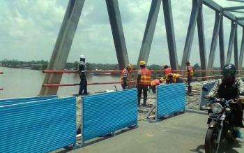PEKERJA : Jalan pada bagian atas jembatan Pulau Telo yang selesai dibongkar sepanjang 100 meter.