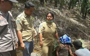 Korban Supodo (kepala ditutup kain) meninggal dunia di lahan perkebunan kelapa sawit diduga akibat tertimpa pohon.