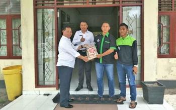 Ketua Pemuda Tani Kotim Abdur Rasid menyerahkan pemesanan beras Jelawat kepada PLT Sekda Kotim Halikinnor dan Kepala Dinas Pariwisata Fajrurahman, Rabu (1/11/2017)