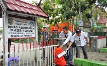 Tersangka pembakar sekolah dasar di Kota Palangka Raya, Suryansyah, memperagakan caranya memasuki SDN 5 Langkai saat rekonstruksi kasus, Rabu (1/11/2017).
