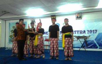 Tim musikalisasi puisi SMAN 4 Palangka Raya, Enggang Voice menerima piala secara simbolis dari Kepala Balai Bahasa Kalteng Haruddin atas keberhasilan tim ini menjadi penampil terbaik II tingkat nasional, Jumat (3/11/2017).