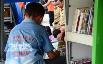 Seorang anak sedang membaca buku di perpustakaan keliling milik Dinas Kearsipan dan Prpustakaan Daerah, Kabupaten Barito Utara, Jumat (3/11/2017).