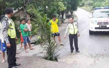 Anggota Satlantas Polres Barut bersama warga sekitar saat menunjukkan jalan berlubang di poros Muara Teweh - Puruk Cahu Km 23.