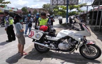 Seorang pengendara ditilang oleh anggota Direktorat Lalu Lintas Polda Kalteng lantaran tidak mengenakan helm saat berkendara di Jalan Rajawali