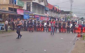 Personel kepolisian berjaga di tempat rekontruksi kasus pembunuhan honorer Dinas Perhubungan Kabupaten Barito Selatan, Ahmad Irfani Akbar, Kamis (9/11/2017).