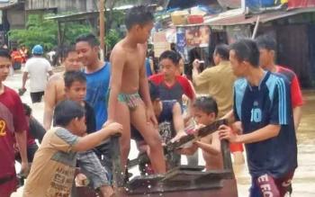 Masyarajat bahu-membahu mengevakuasi warga yang jadi korban banjir di Desa Sikui, Kecamatan Teweh Baru, Kabupaten Barito Utara, Kamis (9/11/2017).