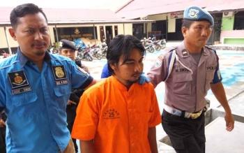 Supian Suri, tersangka kasus pembunuhan, saat digiring aparat Polres Palangka Raya, Kamis (9/11/2017).