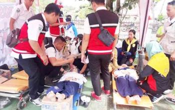 Tim Reaksi Cepat (TRC) Memberikan perawatan pada Peserta Upacara yang Pingsan