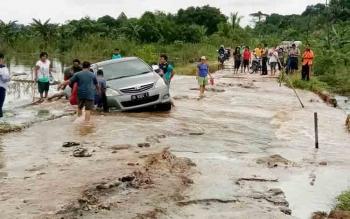 Mobil terperosok karena memaksakan melewati jalan putus di Desa Tabak Kanilan.