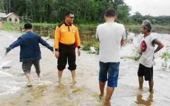 Kapolsek Gunung Bintang Awai, Kabupaten Barito Selatan, Ipda Rahmat Simamora (baju oranye) memantau banjir yang melanda Desa Tabak Kanilan, Jumat (10/11/2017).