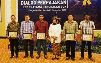 Rimbun Situmorang (paling kiri) mewakili H Abdul Rasyid AS untuk menerima penghargaan kategori 5 besar wajib pajak dengan kontribusi terbesar melalui KPP Pratama Pangkalan Bun.