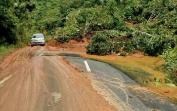 Tampak sebuah minu bus saat melewati ruas jalan negara yang tertimbun material longsor akibat hujan deras di kecamatan Delang, beberapa bulan lalu.