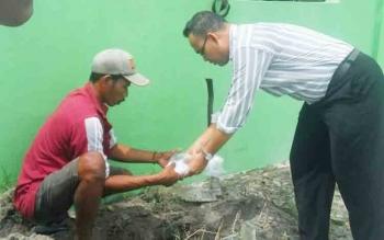 petugas pemakaman sekip bersama Kanit Identifikasi Reskrim Polres Kobar Aiptu Ferdinans Abineno sedang memakamkan jasad janin malang usai diotopsi