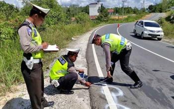 Anggota Satlantas Polres Gunung Mas melakukan olah tempat kejadian perkara di lokasi kecelakaan lalu lintas, Rabu (15/11/2017).