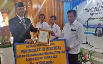 Wakil Bupati Sukamara Windu Subagio menyerahkan penghargaan kepada desa berprestasi.