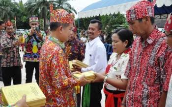 Bupati Kapuas Ben Brahim S Bahat menyerahkan Kitab Agama Hindu Kaharingan kepada Majelis Resort Kaharingan.