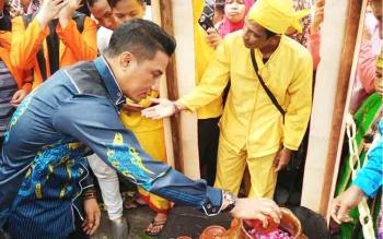 Bupati Kotim Supian Hadi saat mencampur ssembilan air berbeda dari sembilan sungai di Kalteng, pada saat prosesi kegiatan bidaya Mandi Safar.