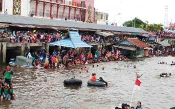 Ribuan warga sedang menonton dan menceburkan diri ke Sungai Mentaya saat kegiata budaya Mandi Safar.