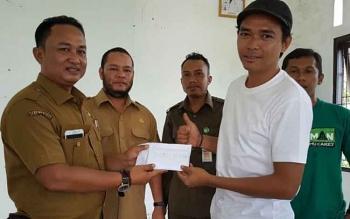 Ajudan Bupati Katingan Fahrozi (kiri) menyerahkan donasi sumbangan kepada ketua panitia Habibi Mubarak disaksikan Ketua Karang Taruna Lutfi Fauzi.