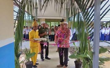 Kepala Bidang Pembinaan SMP memotong tali untuk meresmikan bangunan baru yang ada di SMPN 4 Bataguh.