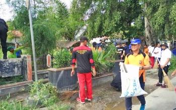 Ditpolair Polda Kalteng Badarudin membawa kantong sampah saat gotong-royong membersihkan Taman Kota Sampit, Jumat (17/11/2017).