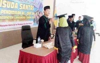 Tampak Wakil Bupati Lamandau, Drs. H. Sugiyarto, saat memindahkan tali toga pada kegiatan wisuda santri TPA se Lamandau, di Aula Bappeda Lamandau, Senin (20/11/2017)