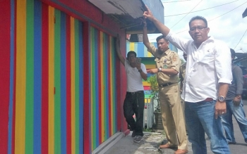 M Yusuf Riyanto (baju putih) Relawan Bersatu dan Kabid Pengelolaa Sampah dan Limbah B3 DLH Kobar M Robiannur menunjukkan contoh dinding luar rumah warga yang sudah di cat warna warni