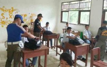Anggota Satpol PP merazia tas siswa SMKN 1 Puruk Cahu.