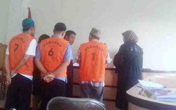 Nordin, Yudiansyah, dan Sugianto (baju jingga), terdakwa kasus pungli di Seruyan Expo, menunjukkan bukti perjanjian sewa stan kepada majelis hakim Pengadilan Negeri Sampit, Rabu (22/11/2017).