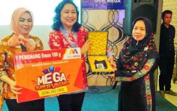 Regional Head Bank Mega Kalimantan Sandhora Alfoncia menyerahkan hadiah 100 gram emas kepada Islamiyah Hamdani, Selasa (21/11/2017) malam
