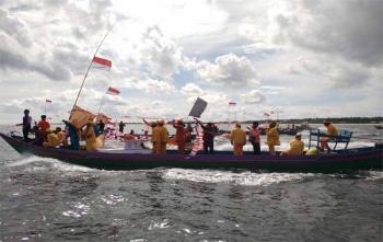 Sejumlah tokoh adat dan juga masyarakat saat membawa prahu kecil yang akan di larungkan di laut Pantai Ujung Pandaran dalam kegiatan tradisi budaya Simah Laut, Minggu (26/11/2017)