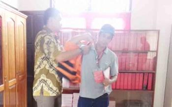 Selwinoto (pakai topi) mantan penjabat Kades Tumbang Bajanei saat memasang rompi tahanan bersama penyidik.