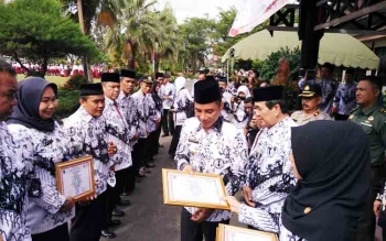 Bupati Kotim Supian Hadi saat memberikan penghargaan kepada guru.