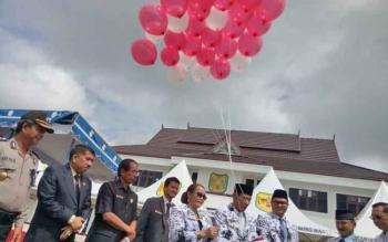 Bupati Gunung Mas Arton S Dohong didampingi istrinya, Apristini, Wakil Bupati Rony Karlos, Ketua DPRD Gumer, melepas balon seusai upacara peringatan Hari Guru Nasional dan HUT ke-72 PGRI di halaman kantor Setda Gunung Mas, Senin (27/11/2017).