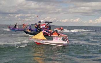 Sejumlah perahu baik itu milik nelayan maupun kepolisian saat memutari perahu kecil yang membawa 44 macam kue tradisional, dalam prosesi kegiatan budaya adat Simah Laut, Minggu (27/11/2017).