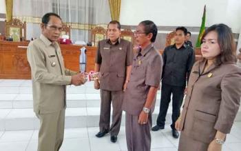 Bupati Arton S Dohong (kiri) menyerahkan Raperda ke Ketua DPRD Gunung Mas Gumer, Selasa (28/11/2017)