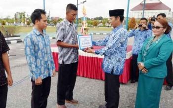 Bupati Gunung Mas Arton S Dohong menyerahkan piala dan uang pembinaan kepada juara lomba pasar desa, Rabu (29/11/2017).